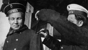 The sailor cuts off the officer's shoulder straps